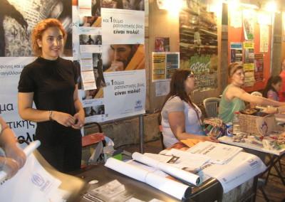 """""""Εθελόντρια της Ύπατης Αρμοστείας του ΟΗΕ για τους Πρόσφυγες συμμετέχει στο 16ο Αντιρατσιστικό Φεστιβάλ Αθήνας, μοιράζοντας υλικό και ενημερώνοντας του συμμετέχοντες για την εκστρατεία «Και 1 θύμα ρατσιστικής βίας είναι πολύ!» και τις δράσεις του Οργανισμού"""" - UNHCR/Ιούλιος 2012"""